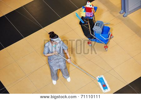 female cleaner with mop and uniform cleaning hall floor of public business building