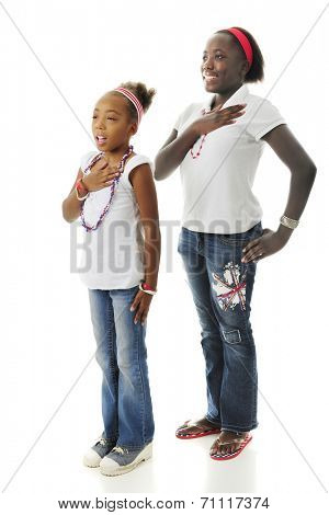 Two African American girls standing with hands over their hearts while saying the Pledge of Allegiance.  On a white background.