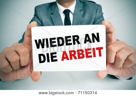 businessman holding a signboard with the text wieder an die arbeit, back to work in german, written in it poster