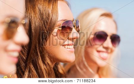 summer vacation, holidays, friendship and people concept - close up of smiling young women in sunglasses