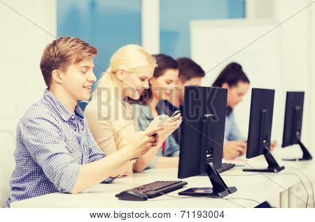 education, techology and internet concept - group of smiling students with computer monitor and smartphones