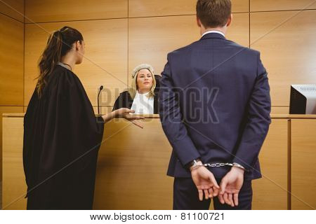 Judge talking with the criminal in handcuffs in the court room