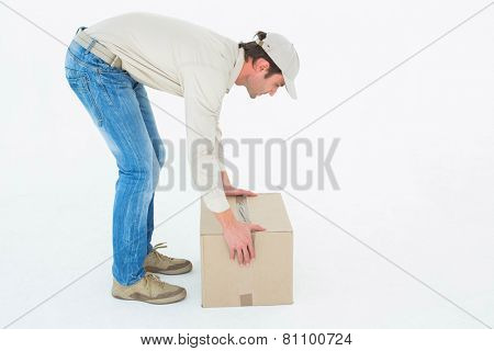 Full length side view of delivery man picking cardboard box against white background