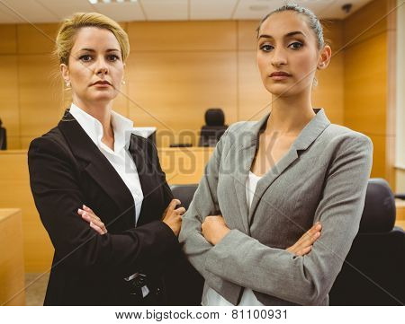 Two serious lawyers standing with arms crossed in the court room