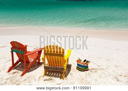 Colorful yellow and orange lounge chairs at tropical beach in Caribbean with beautiful turquoise ocean water and white sand