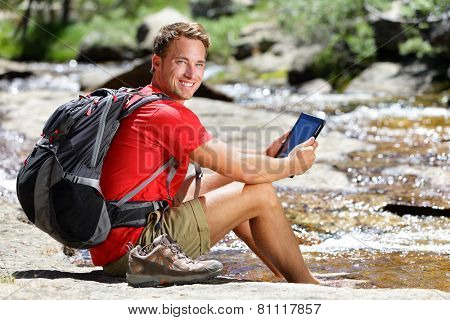 Tablet computer man hiker relaxing by river holding ebook reader reading e book or map, hiking in Yosemite, USA using travel app or map during hike. poster