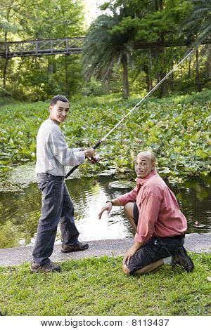 Hispanic Teenager And Father Fishing In Pond