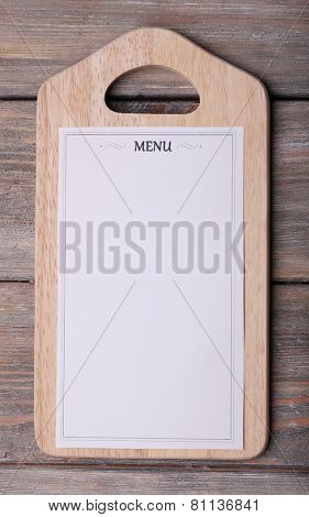 Menu sheet of paper on rustic wooden surface background