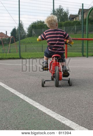Learning to cycle, training wheels and a red bike
