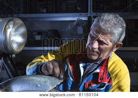 Mechanic Sanding A Mudguard.