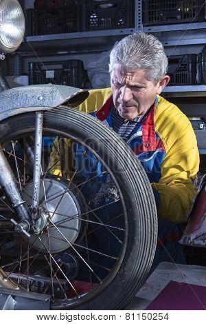 mechanic sanding the motorcycle wheel spokes