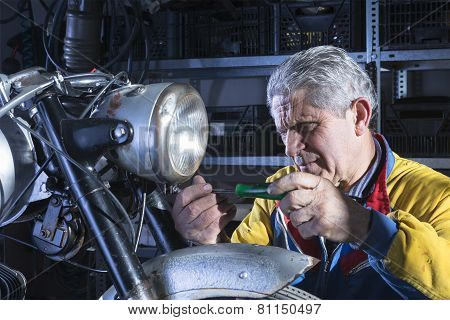 Mechanic Unscrewing The Motorcycle Headlight.
