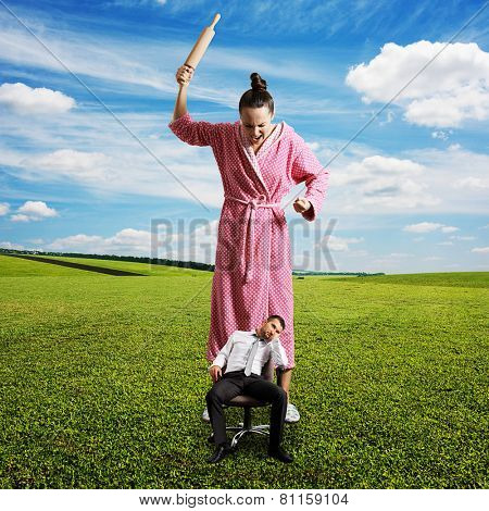 dissatisfied woman with rolling pin screaming at small lazy man on the chair. photo at outdoor