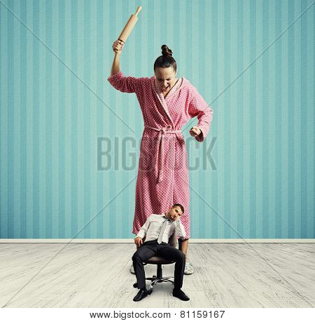 dissatisfied woman with rolling pin screaming at small lazy husband in room with blue wall poster