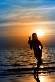 Beautiful Silhouette Of Young Woman In Sea On Sunset Background