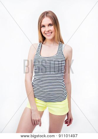Happy woman posing over gray background and looking at camera. Wearing in t-shirt and shorts
