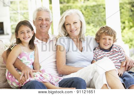 Grandparents And Grandchildren Sitting On Cane Sofa At Home