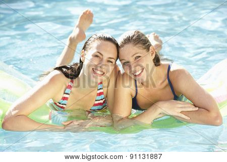 Portrait Of Two Young Women Relaxing In Swimming Pool