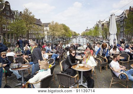 Many People Enjoy Nice Spring Day Outside Near Canal In Amsterdam