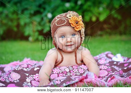 A Cute Little Baby Is Looking Into The Camera And Is Wearing A Brown Hat. The Baby Could Be A Boy Or