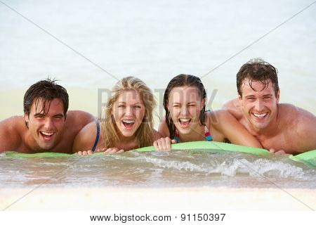 Group Of Friends Having Fun In Sea On Airbed