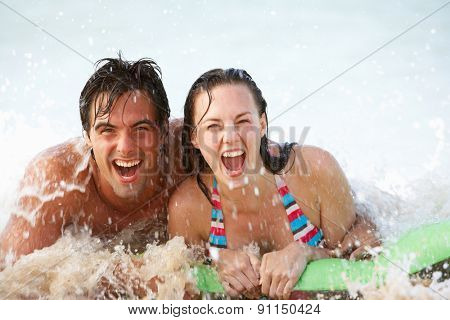 Young Couple Having Fun In Sea On Airbed