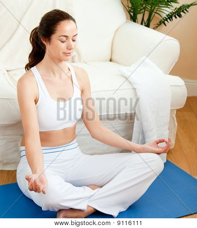 Concentrated Woman Doing Yoga Sitting In Her Living-room