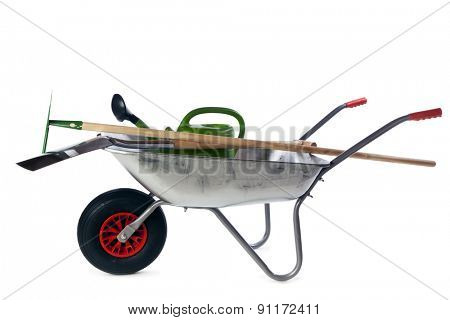 Spade, watering can and garden hoe in wheelbarrow isolated on white background