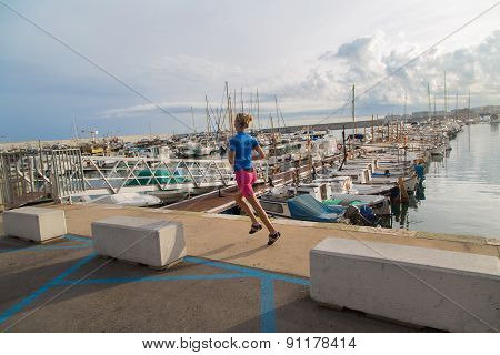 Young Woman Jogging In Harbor In Colorful Sportwear