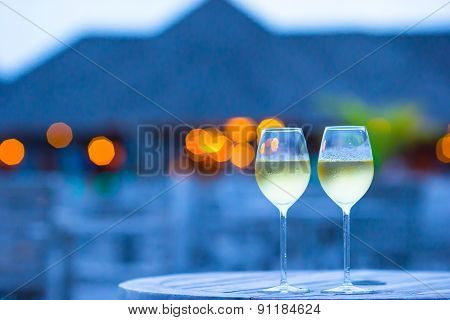 Two glasses of tasty white wine at sunset