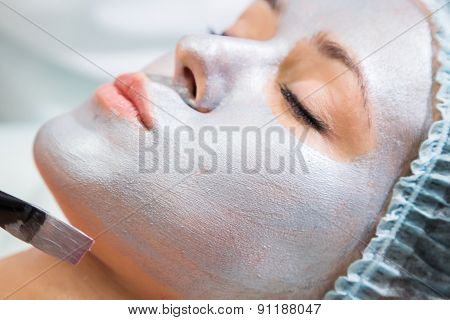 Application of rejuvenating mask on the face of the girl.