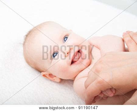 Happy three month baby girl is receiving arm massage from a female massage therapist