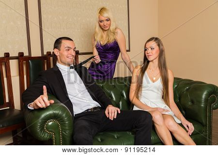 The relationship between man and woman. The concept of a love triangle. Human emotions - jealousy, betrayal, jealousy, love. Two beautiful girls and a guy on a green leather couch. poster
