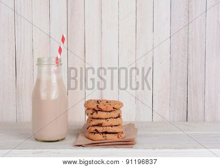 An snack of cookies and milk on a rustic wood set. A small bottle of chocolate milk with a drinking straw and a stack of chocolate chip cookies. Horizontal format with copy space.
