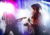 Beautiful woman listening to music with headphones. Live music background with guitar and bright lights on stage. Live music and party concept. poster