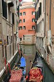 Venetian landscape with gondolas. Canal in Venice with gaily decorated gondolas moored to the berth. poster