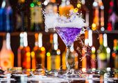 Martini drink with dry ice smoke effect and splash, served on bar counter with blur bottles on background poster