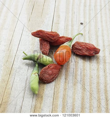 Goji berry dried and fresh isolated on wood background