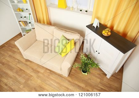 Modern living room interior with beige sofa and white furniture