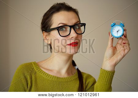 Little Blue Alarm Clock In The Hands Of Young Woman
