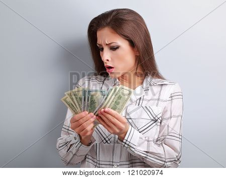 Young Surprising Woman Looking And Counting Her Salary And Thinking How Little Money She Have Earned