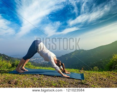 Young sporty fit woman doing yoga asana Adho mukha svanasana - downward facing dog - in Surya Namaskar Sun Salutation outdoors in Himalayas in the morning