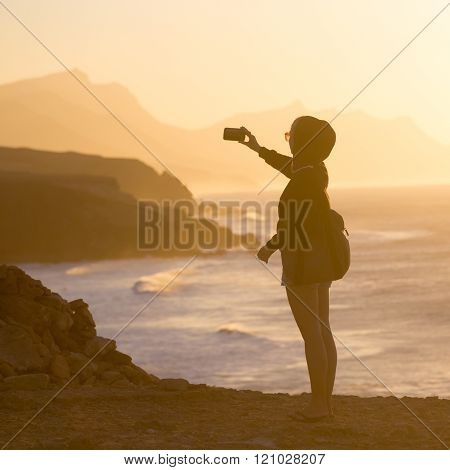 Woman snaping photo of La Pared beach in sunset.