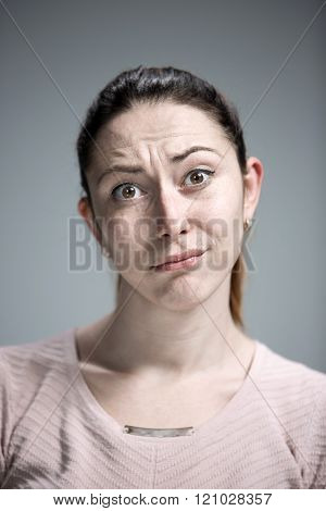 Woman is looking imploring over gray background