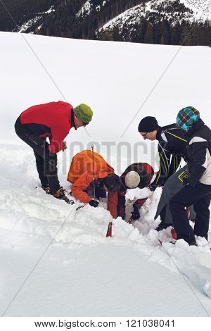 WERTACHER HOERNLE, WERTACH, GERMANY - FEBUARY 28 2016: Team of alpine rescuers digging in snow for a buried victim standing grouped around an excavated hole as they train using new techniques