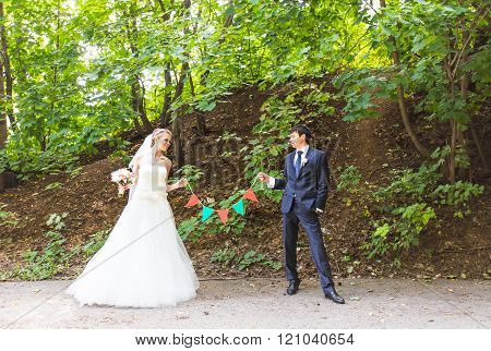 Bride and groom in the park. Garlands decorations