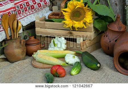 two boxes with vegetables,squash and zucchini ,corn on the cob and tableware made from clay