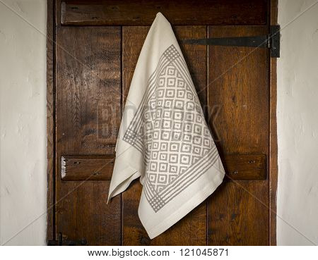 White Towel With Gray Bird's Eye Pattern Hanging On  Door