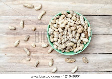 Top view of peanuts in bowl on wooden table