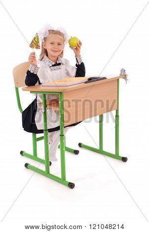 Little Schoolgirl Sitting At A Desk Holding A Piece Of Fruit And Lollipop
